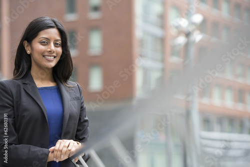 Business People. A Young Woman In A Blue Dress And Grey Jacket.