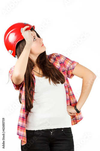 a girl in a red helmet looks up in a shirt in a cell