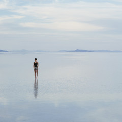A Woman Standing On The Flooded Bonneville Salt Flats, At Dusk.
