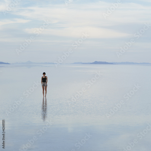 A Woman Standing On The Flooded Bonneville Salt Flats, At Dusk.