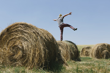 Back View Of A Man Balancing On One Leg On Top Of A Hay Bale.