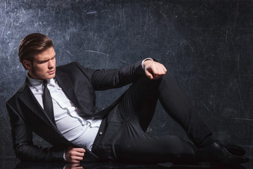 fashion elegant man in black suit and tie lies down