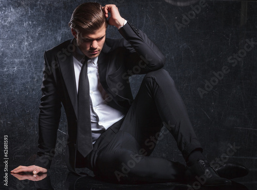 elegant fashion man is looking thoughtful and sad