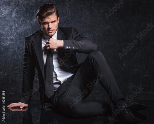 seated fashion man is fixing his black tie