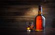 Leinwandbild Motiv bottle and glass of whiskey with ice on a wooden background