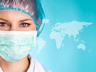 Pretty female doctor in surgical mask and cap over world map