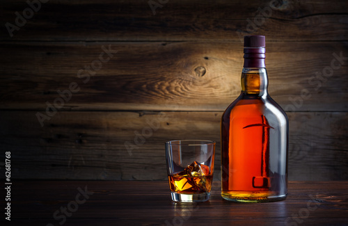 Tuinposter Alcohol bottle and glass of whiskey with ice on a wooden background