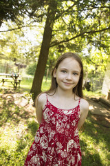 A Young Girl In A Red Floral Summer Dress In The Shade Of Trees.