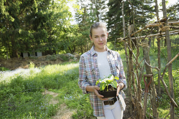 A Girl In A Checked Shirt Holding A Plant With Bright Green Leaves In A Plant Pot. An Fenced Off Enclosure.