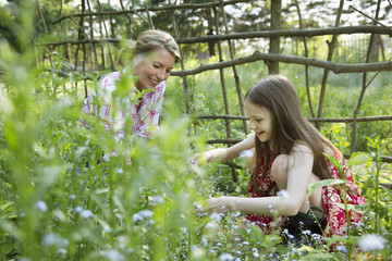 A Mother And Daughter Together In A Plant Enclosure With A Homemade Fence. Picking Flowers And Plants. Green Leafy Foliage.