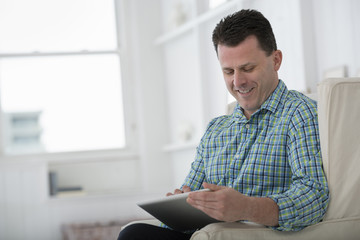 A Man Sitting In An Armchair, Using A Digital Tablet.
