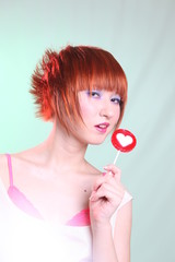 Girl with candy heart on light background