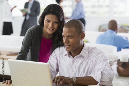 Office. A Man And A Woman Using A Laptop Computer.