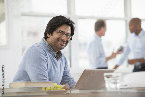 Office Life. A Young Man Sitting Using A Laptop Computer.