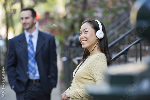 A Woman Wearing Music Headphones, And A Man In A Business Suit.