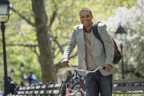 A Family In The Park On A Sunny Day. A Man Pushing A Bicycle.