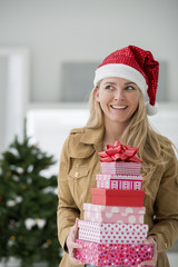 Office Interior. Celebrating Christmas. A Woman In A Santa Hat Holding A Stack Of Presents. Decorated Christmas Tree.