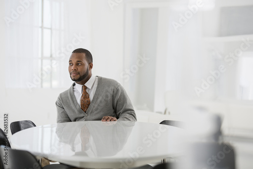 Office Interior. A Man In A Business Suit At A Table Seated At A Table.