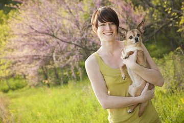 Young Woman In Grassy Field In Spring Holding A Dog