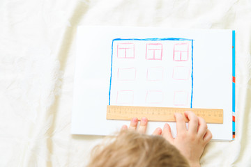 Child designing and measuring a house