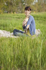 A Young Woman Sitting In A Field, On A Blanket, Holding A Small Chihuahua Dog.