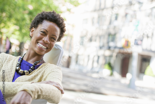City Life. A Woman Sitting In The Open Air In A City Park.