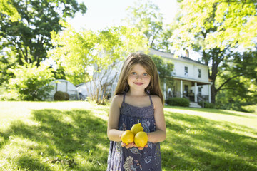 Outdoors In Summer. On The Farm. A Girl In The Garden Holding Three Large Lemon Fruits In Her Hand.