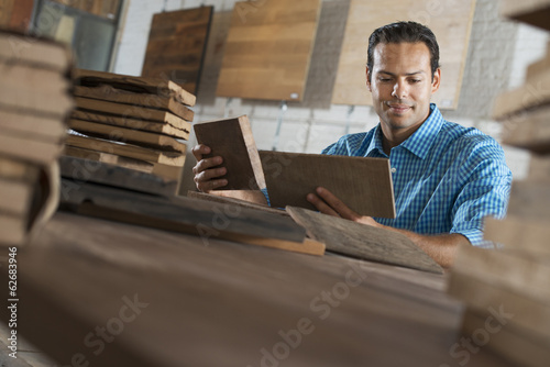 A Young Man In A Workshop. Examining A Reclaimed Wood Sample.