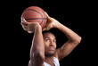 Basketball player throwing the ball against dark background