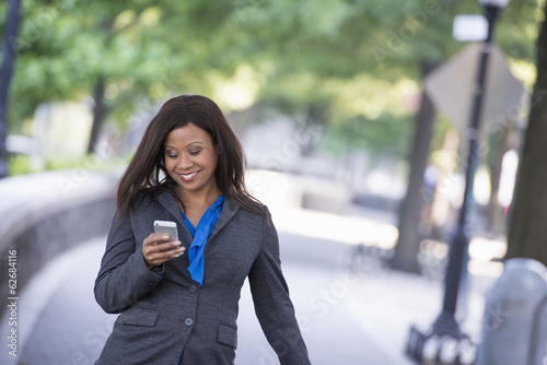Summer. A Woman In A Grey Suit With A Bright Blue Shirt. Using A Smart Phone.