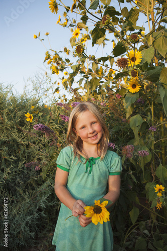 A Girl Standing Outside In A Garden, Holding A Large Sunflower.