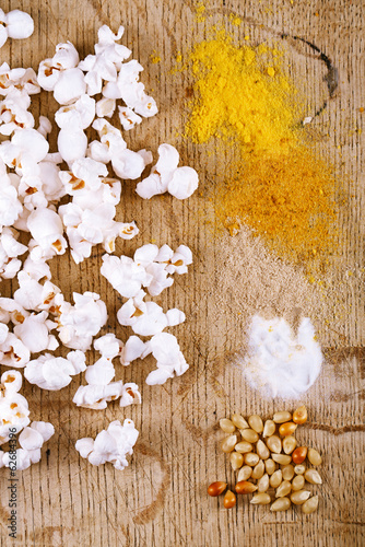 healthy popcorn with defferent type of salt and kernels  on wood