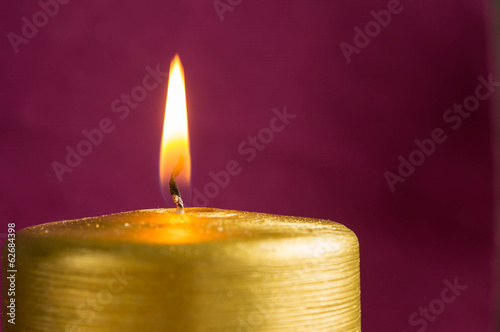 Burning gold candle on a claret background