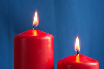 Two burning red candles on a blue background close up