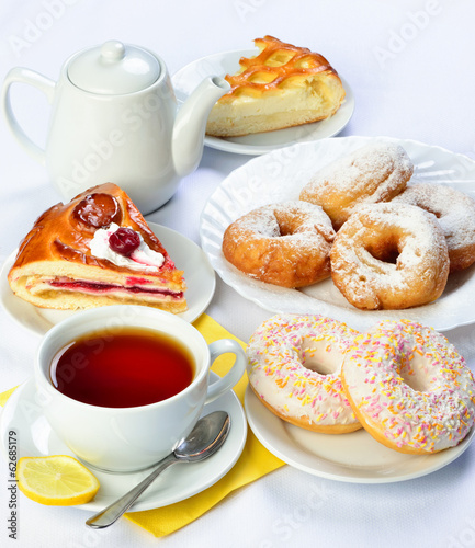 still life of setout table with baking pies, donuts, tee cup and