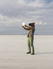 A Man Wearing A Horse Mask, Taking A Photograph With A Tablet Device, On Bonneville Salt Flats.
