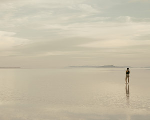 A Woman Standing On The Flooded Bonneville Salt Flats At Dusk. Reflections In The Shallow Water.