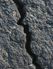 A Lava Field, With Black Solidified Rock Surface, With Fissures.