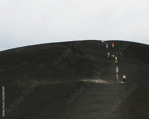 A Black Volcanic Cone Hillside In The Craters Of The Moon National Monument And Preserve In Butte County Idaho. People Walking On The Slope.