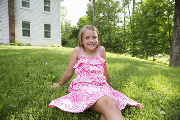 A Young Girl In A Pink Patterned Sundress Sitting On The Grass Under The Trees In A Farmhouse Garden.