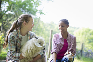 Two Young Girls On The Farm, Outdoors. One With Her Arms Around A Very Fluffy Haired Angora Goat.