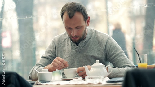 Happy young man adding sugar into tea in cafe