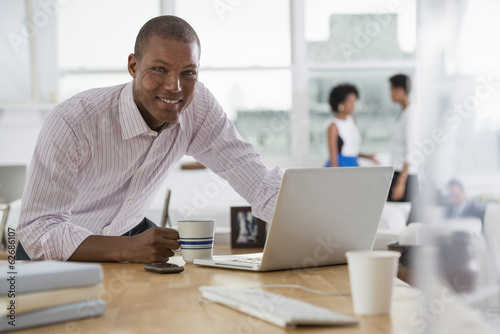 Office. A Young Man Using A Laptop Computer On A Desk.