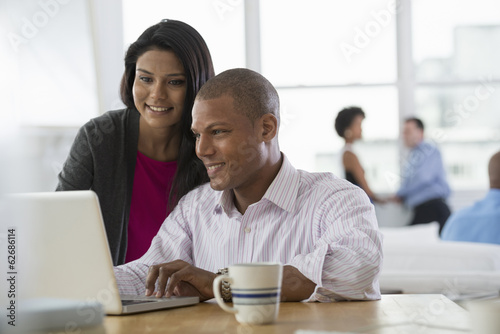 Office. Two People, A Man And A Woman, Sharing A Laptop Computer.