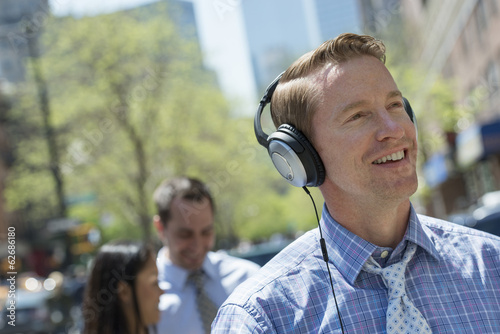 A Man Listening To Music On His Headphones. A Couple In The Background.