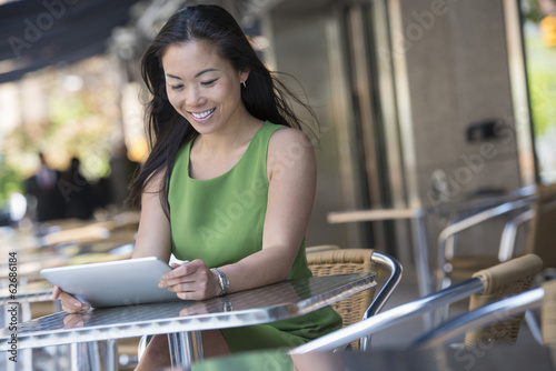 A Woman Sitting Outdoors At A Cafe Table Using A Digital Tablet.