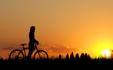 Mountain biker girl silhouette in sunset