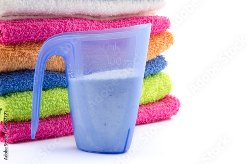 measuring cup filled with soap flakes and piled towels