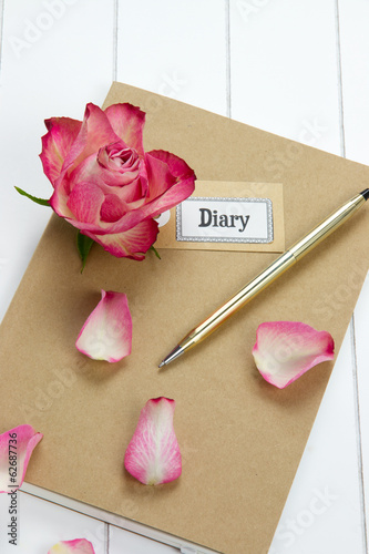 diary with red rose and leaves
