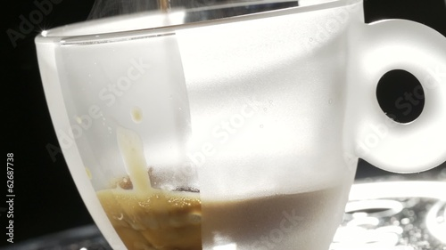 translucent cup of espresso filling up